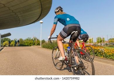 Eindhoven, The Netherlands, September 3rd 2017, Two women race cycling through Eindhoven with the Evoluon in the background on a sunny day