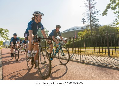 Eindhoven, The Netherlands, September 3rd 2017, A group of women doing sports race cycling through Eindhoven with the Evoluon in the background on a sunny morning