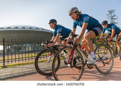 Eindhoven, The Netherlands, September 3rd 2017, A group of women doing sports race cycling through Eindhoven with the Evoluon in the background on a sunny day