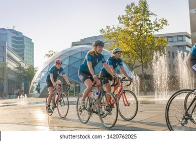 Eindhoven, The Netherlands, September 3rd 2017, A group of women race cycling through Eindhoven on the 18 Septemberplein with a round building and water in the background on a sunny day