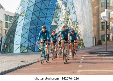 Eindhoven, The Netherlands, September 3rd 2017, A group of women race cycling through the streets of Eindhoven with a building in the background on a sunny day