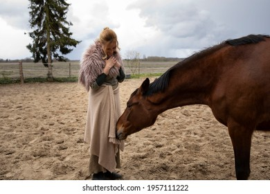 Eine Frau Anfang 40, füttert ihr Pferd mit den Möhren, sie hat einen Korb an der Hand, der Kopftuch, eine Decke über die Schulter. Es ist April, der Stahl ist aus dem Holz. Frau kuschelt mit Pferd - Shutterstock ID 1957111222