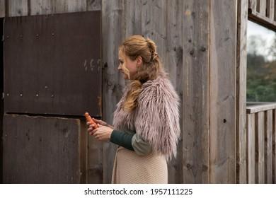 Eine Frau Anfang 40, füttert ihr Pferd mit den Möhren, sie hat einen Korb an der Hand, der Kopftuch, eine Decke über die Schulter. Es ist April, der Stahl ist aus dem Holz. Frau kuschelt mit Pferd - Shutterstock ID 1957111225