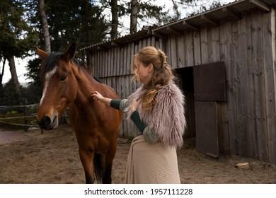 Eine Frau Anfang 40, füttert ihr Pferd mit den Möhren, sie hat einen Korb an der Hand, der Kopftuch, eine Decke über die Schulter. Es ist April, der Stahl ist aus dem Holz. Frau kuschelt mit Pferd - Shutterstock ID 1957111228