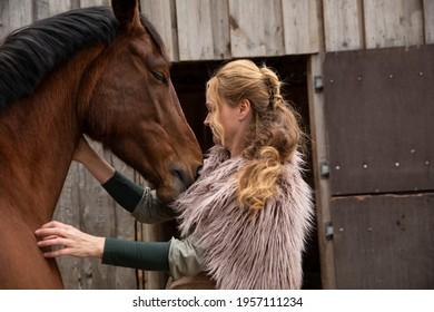 Eine Frau Anfang 40, füttert ihr Pferd mit den Möhren, sie hat einen Korb an der Hand, der Kopftuch, eine Decke über die Schulter. Es ist April, der Stahl ist aus dem Holz. Frau kuschelt mit Pferd - Shutterstock ID 1957111234