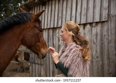 Eine Frau Anfang 40, füttert ihr Pferd mit den Möhren, sie hat einen Korb an der Hand, der Kopftuch, eine Decke über die Schulter. Es ist April, der Stahl ist aus dem Holz. Frau kuschelt mit Pferd - Shutterstock ID 1957111237