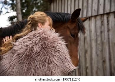 Eine Frau Anfang 40, füttert ihr Pferd mit den Möhren, sie hat einen Korb an der Hand, der Kopftuch, eine Decke über die Schulter. Es ist April, der Stahl ist aus dem Holz. Frau kuschelt mit Pferd - Shutterstock ID 1957111240