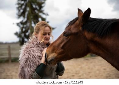 Eine Frau Anfang 40, füttert ihr Pferd mit den Möhren, sie hat einen Korb an der Hand, der Kopftuch, eine Decke über die Schulter. Es ist April, der Stahl ist aus dem Holz. Frau kuschelt mit Pferd - Shutterstock ID 1957111243