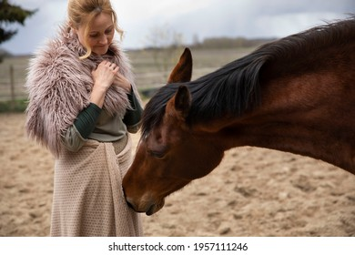 Eine Frau Anfang 40, füttert ihr Pferd mit den Möhren, sie hat einen Korb an der Hand, der Kopftuch, eine Decke über die Schulter. Es ist April, der Stahl ist aus dem Holz. Frau kuschelt mit Pferd - Shutterstock ID 1957111246