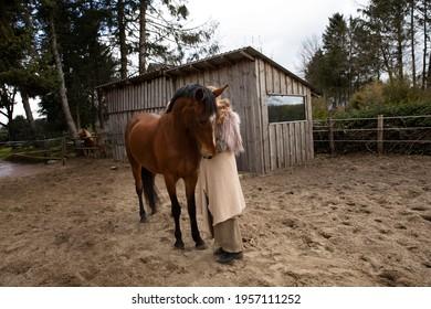 Eine Frau Anfang 40, füttert ihr Pferd mit den Möhren, sie hat einen Korb an der Hand, der Kopftuch, eine Decke über die Schulter. Es ist April, der Stahl ist aus dem Holz. Frau kuschelt mit Pferd - Shutterstock ID 1957111252