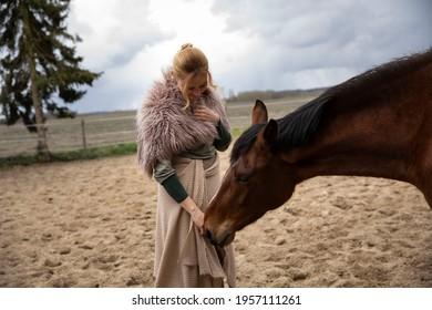 Eine Frau Anfang 40, füttert ihr Pferd mit den Möhren, sie hat einen Korb an der Hand, der Kopftuch, eine Decke über die Schulter. Es ist April, der Stahl ist aus dem Holz. Frau kuschelt mit Pferd - Shutterstock ID 1957111261