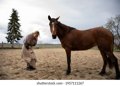 Eine Frau Anfang 40, füttert ihr Pferd mit den Möhren, sie hat einen Korb an der Hand, der Kopftuch, eine Decke über die Schulter. Es ist April, der Stahl ist aus dem Holz. Frau kuschelt mit Pferd - Shutterstock ID 1957111267