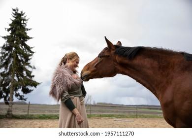 Eine Frau Anfang 40, füttert ihr Pferd mit den Möhren, sie hat einen Korb an der Hand, der Kopftuch, eine Decke über die Schulter. Es ist April, der Stahl ist aus dem Holz. Frau kuschelt mit Pferd - Shutterstock ID 1957111270