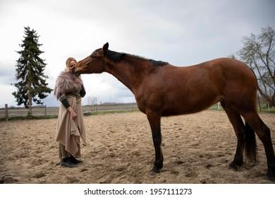 Eine Frau Anfang 40, füttert ihr Pferd mit den Möhren, sie hat einen Korb an der Hand, der Kopftuch, eine Decke über die Schulter. Es ist April, der Stahl ist aus dem Holz. Frau kuschelt mit Pferd - Shutterstock ID 1957111273
