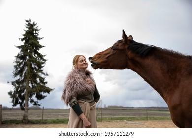 Eine Frau Anfang 40, füttert ihr Pferd mit den Möhren, sie hat einen Korb an der Hand, der Kopftuch, eine Decke über die Schulter. Es ist April, der Stahl ist aus dem Holz. Frau kuschelt mit Pferd - Shutterstock ID 1957111279