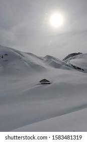 Einsame Hütte auf dem Berg fast komplett mit Schnee bedeckt und hoch oben die Sonne wie ein Spotlight