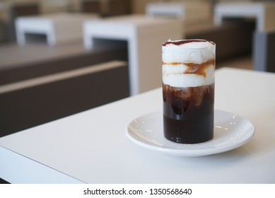 Einspanner coffee. A cup of americano coffee topped with fresh cream, whipped cream and cocoa powder on white plate at cafe. (Copy space, isolated)