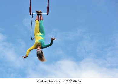 eire square, Galway, Ireland July , art Festival 2017, Mobile Home, trapeze girl artist hanging upside down with legs 100 ft high, smiling with open harms