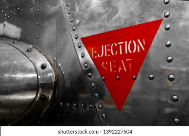 Ejection seat warning sign on the side of an airplane.