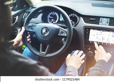 Ejpovice, Czech Republic - August 30 2018: SKODA OCTAVIA interior - Driver holds the steering wheel. Passenger touches the screen of the navigation system