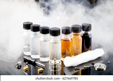 E-juice bottles with tools and smoke on black background