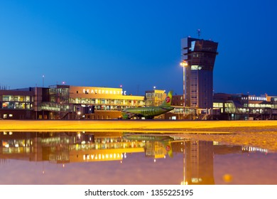 Ekaterinburg, Koltsovo Airport / Russia - 07.26.2018. Passenger terminal building, Air Traffic Control Tower and airfield during the night. Airbus A320 aircraft of S7 Airlines with reflection.
