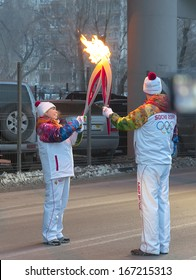 EKATERINBURG, RUSSIA - December 14 2013 - Two torchbearers carried Olympic fire in Ekaterinburg on Moskovskaya street December 14 2013