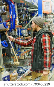 EKATERINBURG, RUSSIA - JANUARY, 8, 2018: A young man chooses hand saws in the hardware store