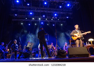 "Ekaterinburg, Russia - November 03, 2018: David Arthur Brown (Brazzaville) performs on stage at the ""Ural"" cultural center. The singer plays the guitar along with a symphony orchestra"