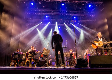 Ekaterinburg, Russia - November 03, 2018: David Arthur Brown (Brazzaville) performs on stage. The singer plays the guitar along with symphony orchestra