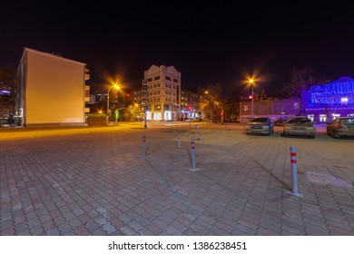 Ekaterinburg, Russia - November 11, 2018: Night Ekaterinburg city without people, sidewalk with gray and pink paving slabs. Yellow and blue shades