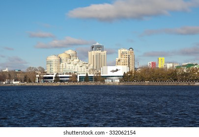 """EKATERINBURG, RUSSIA -  OCTOBER 21, 2015: Photo of Concert Hall """"Cosmos"""" and modern buildings. Waterfront city pond."""