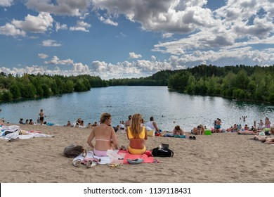 EKERO, SWEDEN - JULY 10, 2018: Two young woman and many people sunbathing and having picnic on a beach with a lake, forest and blue sky with clouds in the background in Ekero Sweden July 10, 2018.