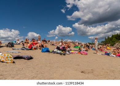 EKERO, SWEDEN - JULY 10, 2018: Low angle front view of many people sunbathing and having picnic on a beach with blue sky and clouds in the background in Ekero Sweden July 10, 2018.