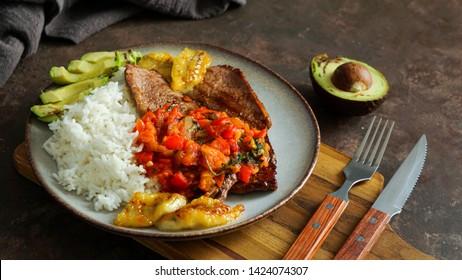 El Bistec a la Criolla - plato colombiano tradicional - carne de buey con salsa de tomates, arroz, aguacate, papas fritas