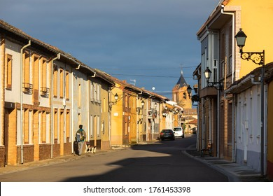 EL BURGO RANERO / Léon / Spain - 10/21/2019: Pilgrim walks on a sunny morning through the streets of El Burgo Ranero, a stretch of the Camino de Santiago de Compostela in Spain.