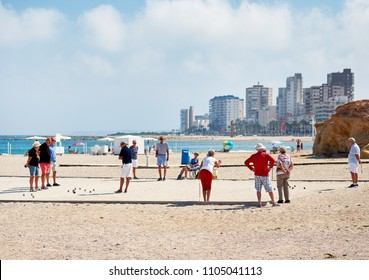 El Campello, Spain - May 22, 2018: Petanque seniors old players on the El Campello sandy beach, skyline city, cloudy day. Petanque is popular game for spanish pensioners aged peoples. Alicante. Spain