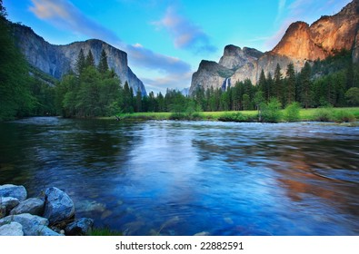 El Capitan and the Cathedral Rocks (with Bridalveil Falls) seen from the Merced River at dusk.