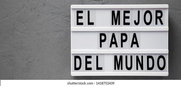 'El Mejor Papa Del Mundo' words on a modern board over gray surface. Overhead, from above, flat lay. Father's day. Copy space.