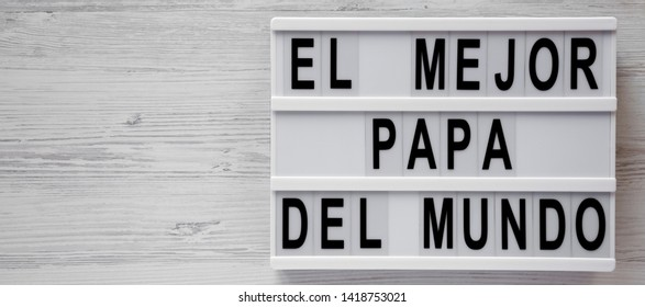 'El Mejor Papa Del Mundo' words on a lightbox over white wooden background, top view. Overhead, from above, flat lay. Father's day. Copy space.