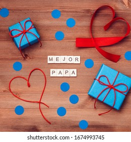 El mejor papa del mundo words made of wooden blocks with blue gift boxes and red hearts on wooden background. Happy fathers day greeting card, holiday flat lay, top view