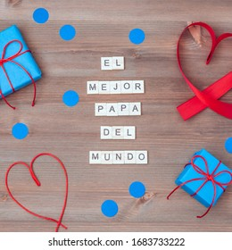 El mejor papa del mundo words that mean best dad in the world made of wooden blocks with blue gift boxes and red hearts on wooden background. Happy fathers day greeting card, holiday flat lay