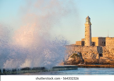El morro fortress and lighthouse of Havana at sunset with huge sea waves crashing on the Malecon seawall