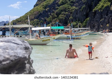 El Nido, Palawan - 26FEB2019 - Island hopping boats moored along a beautiful sandy beach in El Nido, Palawan..