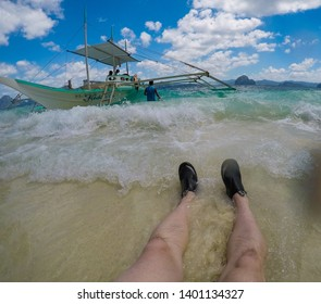 El Nido, Palawan - 26FEB2019 - Travel photo of mans legs in the surf of beach with boat in background.