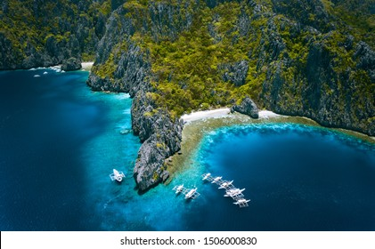 El Nido, Palawan, Philippines. Aerial view of Miniloc Island with diving boats above coral reef surrounded by karst limestone rugged mountain cliffs