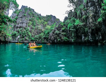 El Nido / Palawan / Philippines - December 2017: Tourists kayaking in the crystalline waters of Small Lagoon, Miniloc Island.