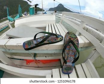 El Nido / Palawan / Philippines - December 2017: Beautiful landscape scenery in El Nido. Summer shoes, beach sandals, Havaianas in the Filipino wooden boat.