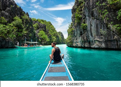 El Nido, Palawan, Philippines, traveler sitting on boat deck exploring the natural sights around El Nido on a sunny day.