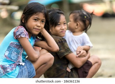 EL NIDO, PHILIPPINES, JANUARY 11 : Kids of a poor filipino family are sitting outdoor, one is holding her  young sister, El Nido, Philippines, on january 11, 2014